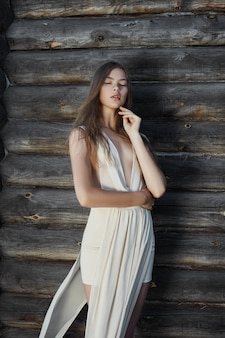 Sexy jeune femme vêtue d'une robe blanche légère posant dans le village près de la vieille maison. fille avec une silhouette parfaite sur le fond d'une maison de campagne en rondins