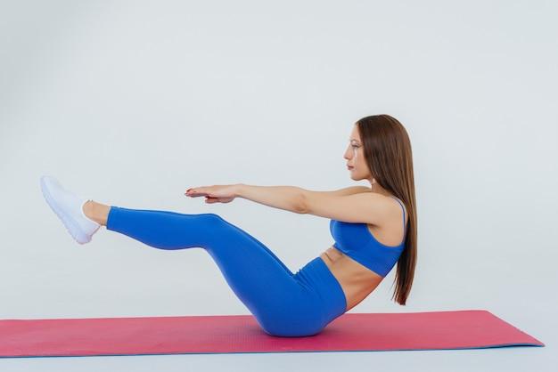Sexy jeune fille effectue des exercices sportifs sur un mur blanc. fitness, mode de vie sain.