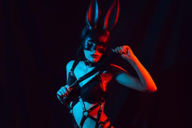 Sexy jeune fille en masque de lapin en lingerie avec ceinture en cuir et fouet