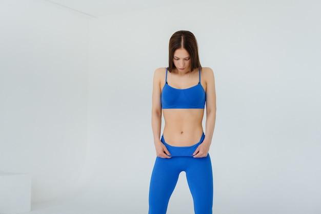 Sexy jeune fille posant dans un survêtement bleu sur un mur blanc. fitness, mode de vie sain.