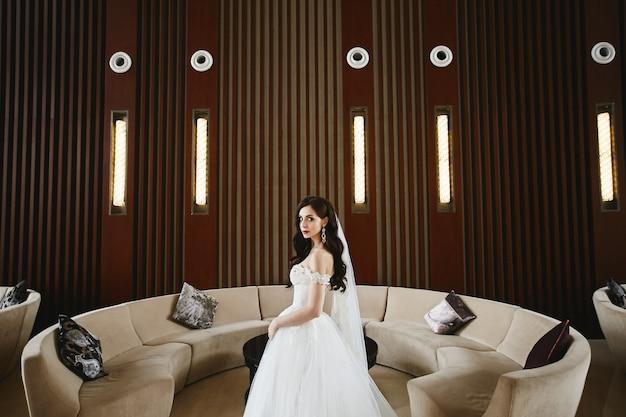 Sexy et jeune mannequin femme avec un corps parfait et de gros seins dans la robe de mariée à la mode avec des épaules nues posant à l'intérieur de luxe moderne