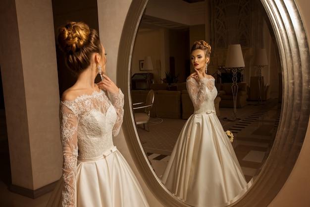 Sexy jeune mariée blonde en robe de mariée en regardant le miroir