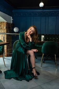 Sexy jolie jeune femme vêtue d'une robe longue verte posant sur une chaise au café de la ville