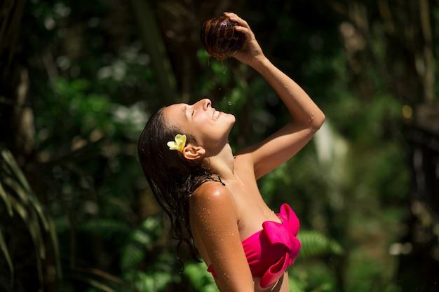 Sexy mince jeune femme brune s'arrosant avec du lait de coco frais à la jungle verte sauvage. royal tropical resort se détendre.