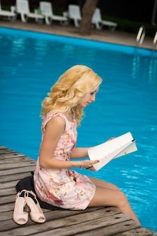 Sexy mince magnifique jeune blonde lit le menu du restaurant au bord de la piscine dans un hôtel de luxe