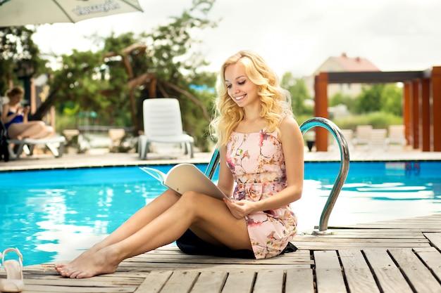 Sexy mince magnifique jeune blonde lit le menu du restaurant au bord de la piscine dans un hôtel de luxe.