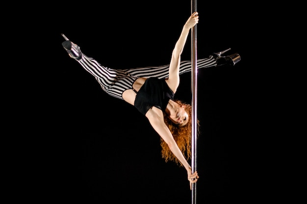 Sexy pole dance girl exerce et pose sur le pylône