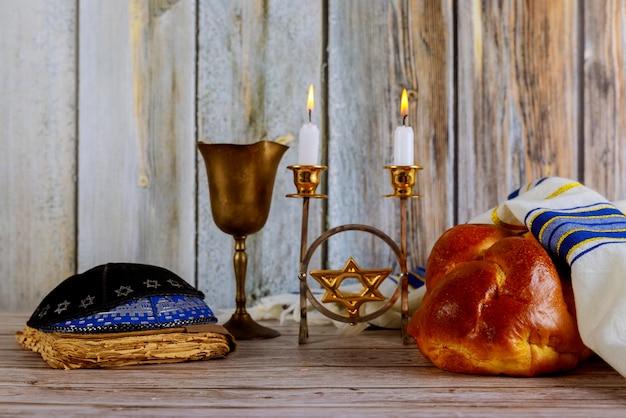Shabbat avec pain challah sur une table en bois, bougies et tasse de vin.