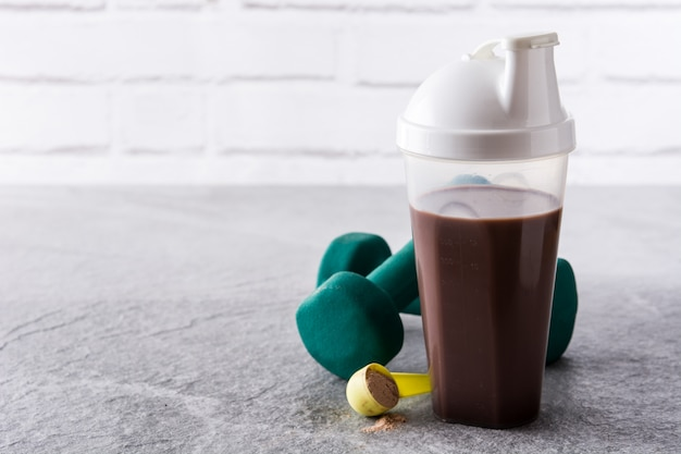 Shake protéiné au chocolat et haltères sur pierre grise