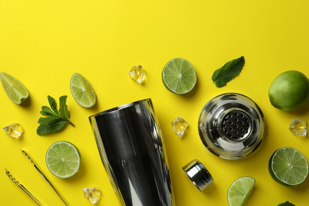 Shaker à cocktail et ingrédients pour mojito sur fond jaune