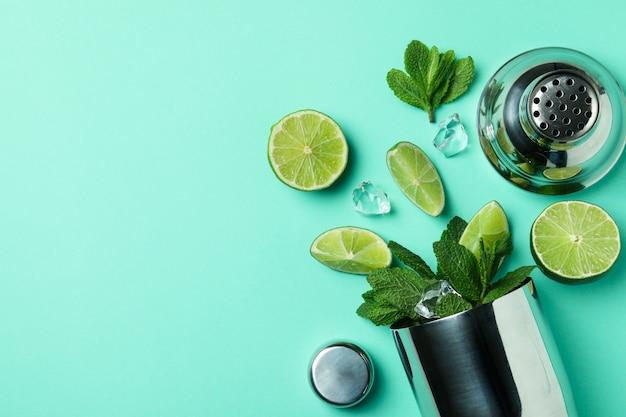 Shaker à cocktail et ingrédients pour mojito sur fond de menthe
