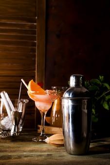 Shaker à cocktail, swizzle, pinces et cuillère à glace dans un seau pour préparer un cocktail d'été