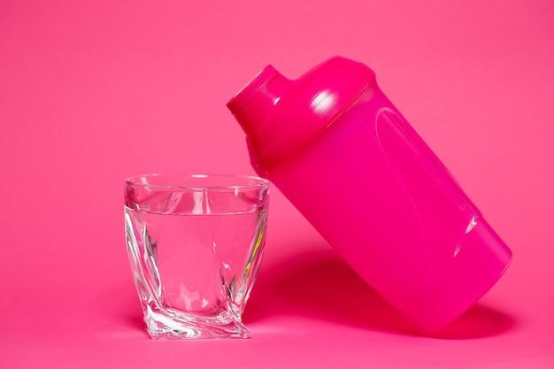 Shaker rose, verre d'eau, fond coloré, sports, boisson énergisante, équipement de gym