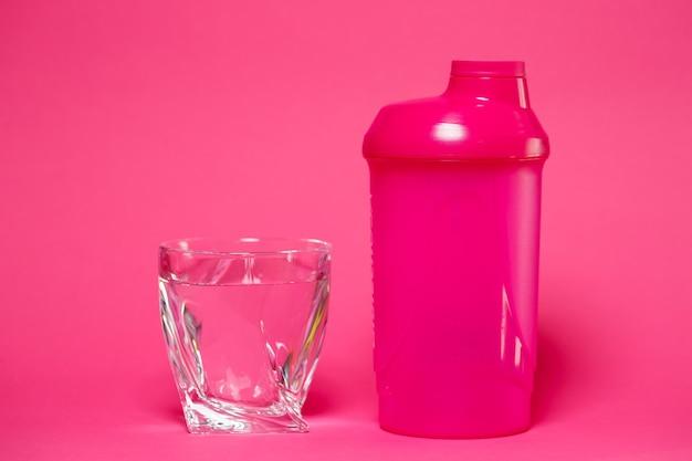 Shaker rose, verre d'eau, fond coloré, sports, boisson énergisante