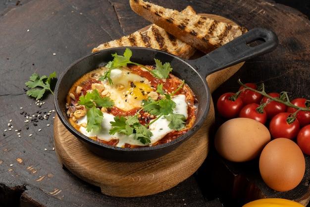 Shakshuka de style chef. un plat israélien classique d'œufs frits dans une sauce de tomates, de piments forts, d'oignons et d'épices.