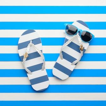 Shales rayés et lunettes de soleil bleu-blanc. vue de dessus, pose à plat.