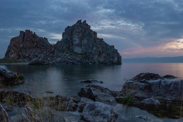 Shaman's rock au-dessus de la surface de l'eau du lac baïkal au coucher du soleil