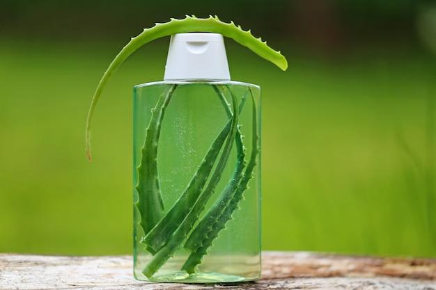 Shampooing bio à l'aloe vera. feuilles d'aloe vera dans une bouteille de shampoing transparent
