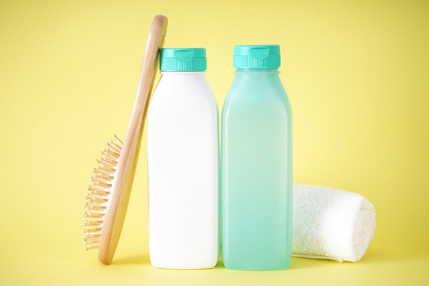 Shampooing, bouteille de revitalisant et brosse à cheveux en bois sur fond jaune.