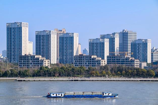 Shanghai, chine - 18 février 2021 : la rivière huangpu à shanghai, chine avec un cargo transférant des marchandises. les gratte-ciel modernes du bund sont en arrière-plan.
