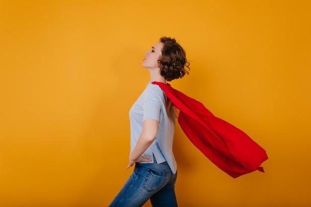 Shapely jeune femme avec manteau rouge en agitant debout