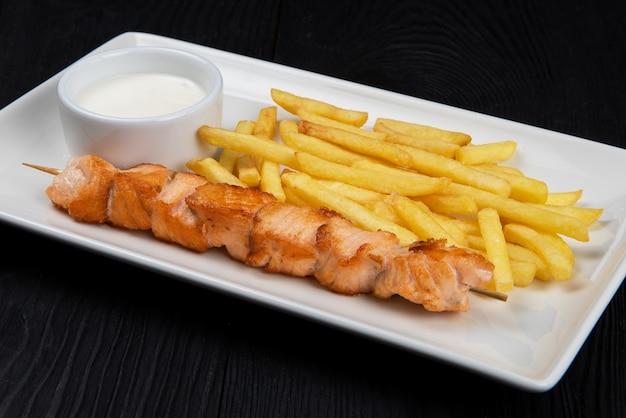 Shashlik de poisson saumon grillé avec pommes de terre frites et sauce sur plaque blanche sur fond de bois noir