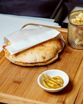 Shaurma servi sur un bureau avec des frites et du poivre mariné
