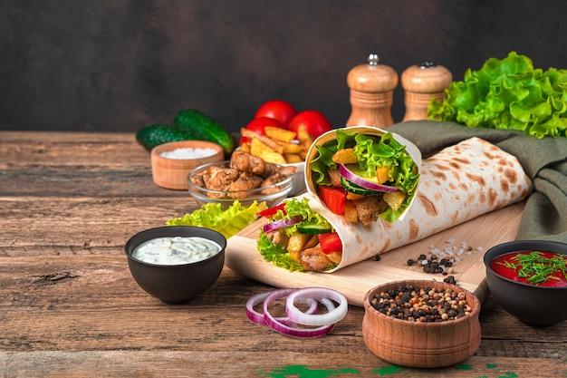 Shawarma au poulet avec frites, légumes, oignons et laitue sur un mur marron. vue latérale, copiez l'espace.