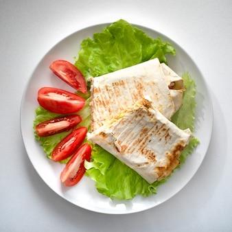 Shawarma coupé en deux sur une feuille de salade, et aux tomates dans une assiette blanche sur fond blanc.