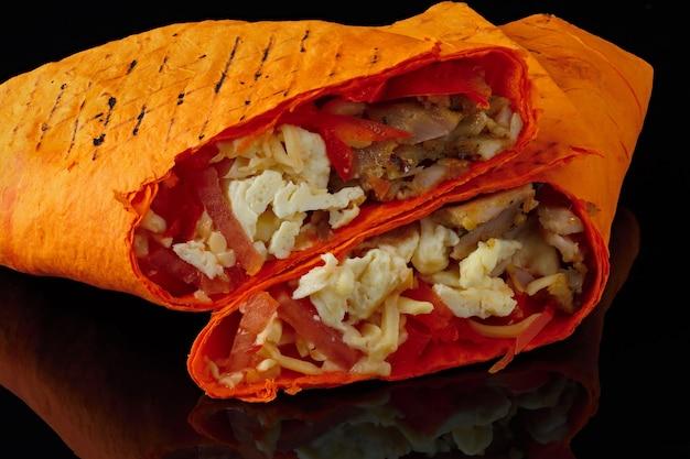 Shawarma dans du pain pita est coupé et repose sur un fond noir réfléchissant. le plat du moyen-orient est préparé sur le grill et servi avec une sauce.
