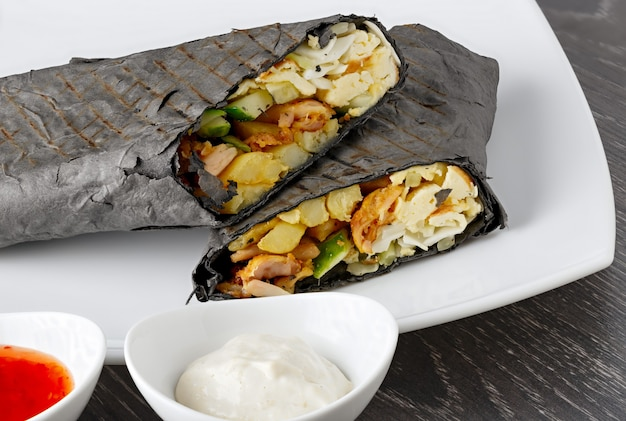 Shawarma dans du pain pita est coupé et se trouve sur une plaque blanche