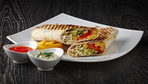 Shawarma dans le pain pita est coupé et se trouve sur une plaque blanche
