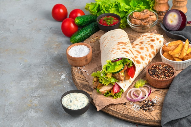Shawarma avec dinde, frites et légumes frais sur un mur gris. vue latérale, copiez l'espace.