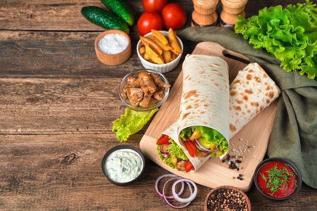 Shawarma avec dinde, tomates, concombre et laitue sur un mur marron avec espace pour copier. fast food.