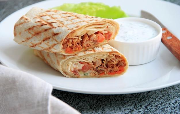 Shawarma avec du poulet, des légumes et des herbes sur une assiette blanche à côté de la sauce et du couteau