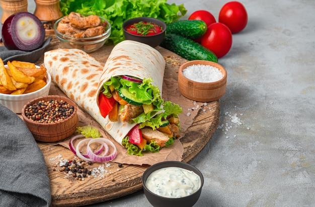 Shawarma et ingrédients sur un mur gris avec un espace pour copier. vue latérale, horizontale.