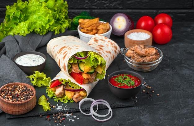 Shawarma et ingrédients sur un mur noir. vue latérale, copiez l'espace.