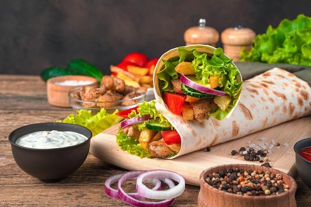 Shawarma juteux avec des légumes frais, de la viande et des frites sur un mur en bois marron. vue latérale, copiez l'espace.