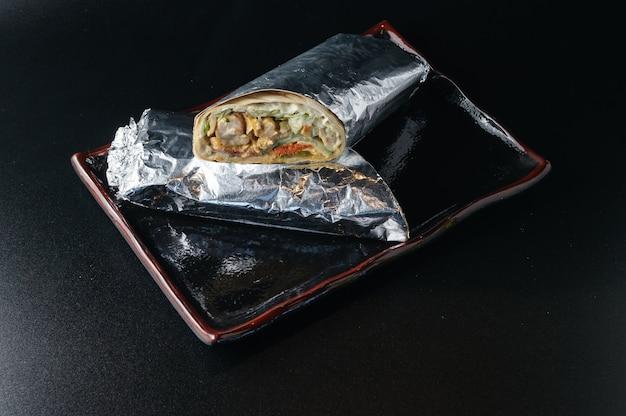 Shawarma lavash frais et chaud avec de la viande enveloppée dans du papier d'aluminium