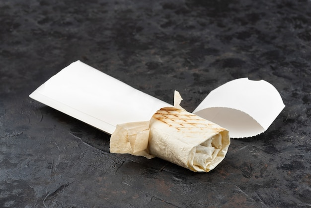 Shawarma oriental traditionnel en carton écologique. surface de pierre sombre. concept de paquets écologiques de matières recyclables. copier l'espace