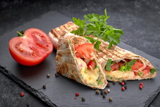 Shawarma pan coupé, avec sauce, tomates, fromage, herbes et ail, sur ardoise noire, sur fond noir