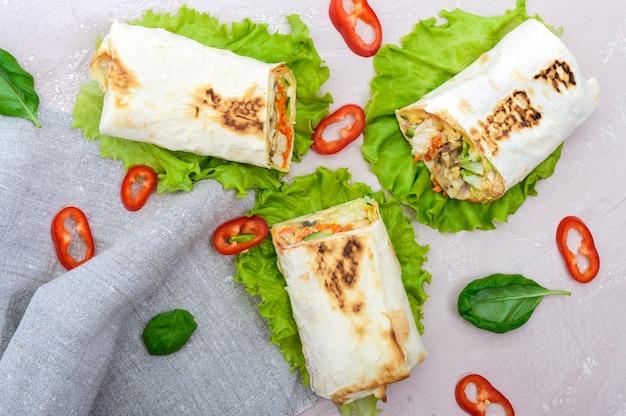 Shawarma - plat du moyen-orient à base de lavash, farci de poulet, champignons, salade de légumes frais, sauce