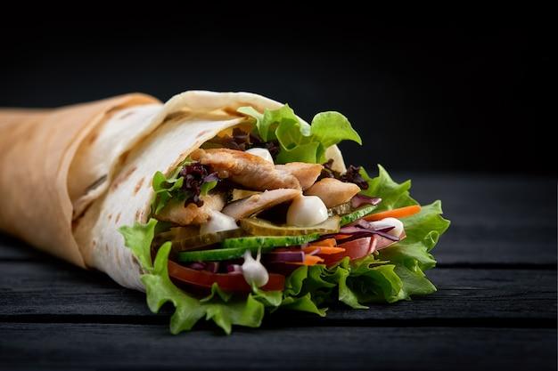 Shawarma roulé dans du lavash, de la viande grillée humide avec de l'oignon, des herbes et des légumes sur fond noir en bois.