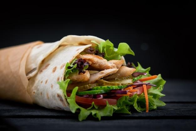 Shawarma roulé dans du lavash, viande grillée humide avec oignon, herbes et légumes sur fond noir en bois.