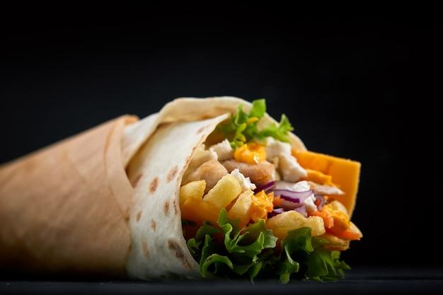 Shawarma roulé dans du lavash, de la viande grillée humide avec de l'oignon, des herbes et des légumes sur une surface noire en bois