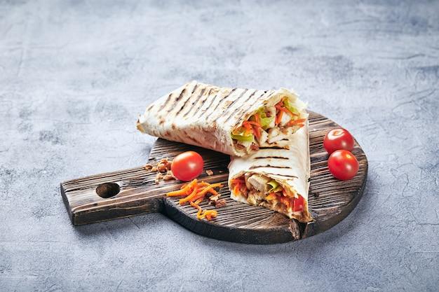 Shawarma traditionnel de l'est avec du poulet et des légumes, doner kebab avec des sauces sur une planche à découper en bois. fast food. nourriture orientale.