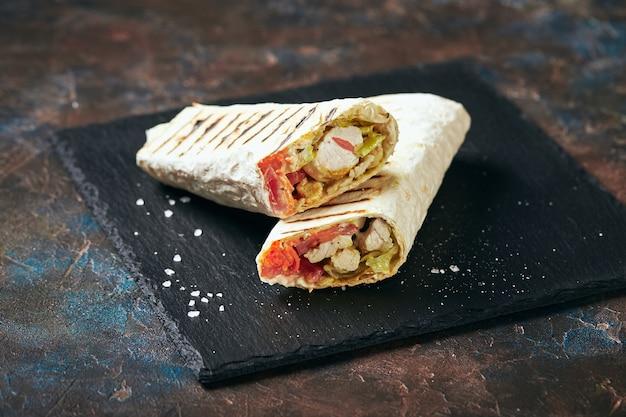 Shawarma traditionnel oriental avec poulet et légumes, doner kebab avec sauces sur ardoise. fast food. nourriture orientale.