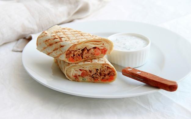 Shawarma avec de la viande dans une assiette blanche