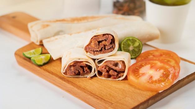 Shawarma avec viande, mayonnaise, tomate et citron vert sur une planche à découper en bois
