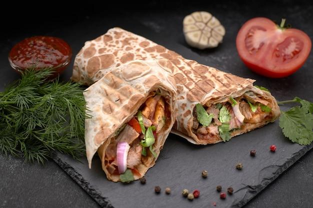 Shawarma à la viande, pan coupé, avec sauce, tomates, fromage, herbes et ail, sur ardoise noire, sur fond noir